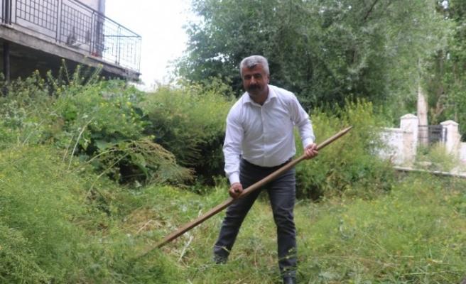 Çim biçme makinesi bozulunca belediye başkanı tırpanı eline aldı