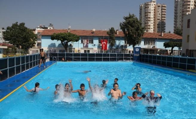 Mersin'de çocuklar okul bahçelerine kurulan portatif havuzlarda yüzme öğreniyor