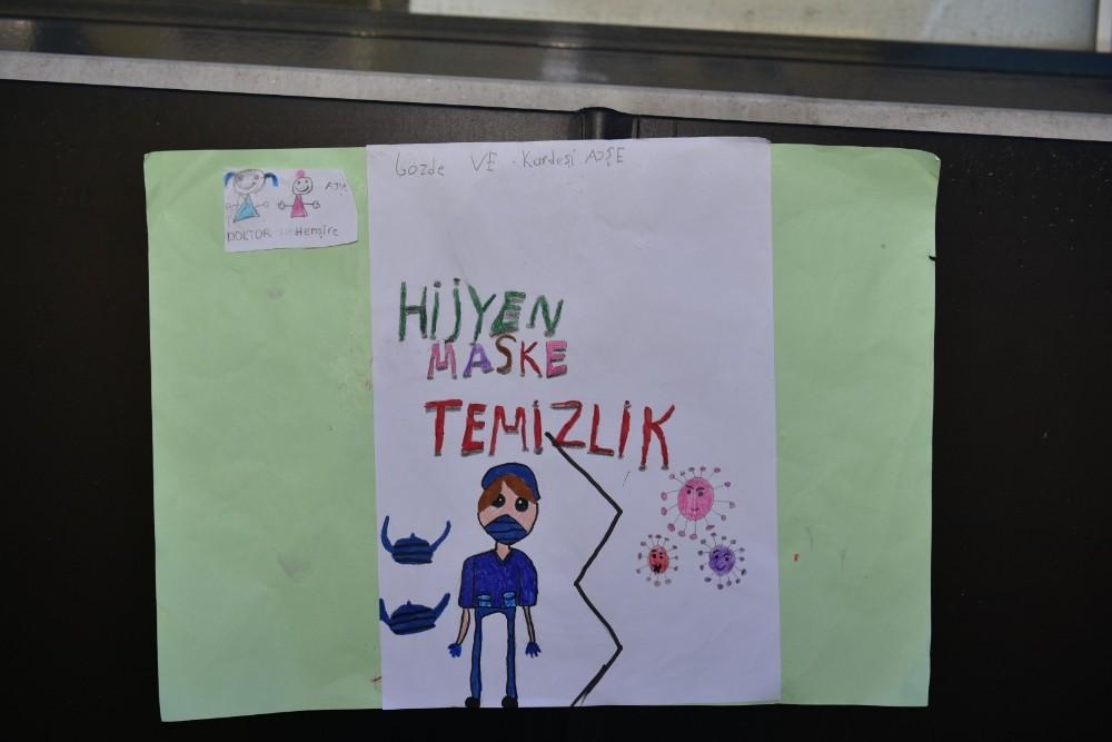 Tuzla'da 2 kardeş okulların açılması için bilboardlara kendi yaptıkları afişleri astı
